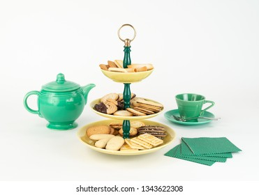 Three Tier  Mid-Century Modern Serving Dish with Yellow Glazed Plates  and Green Bakelite Stem with Brass Ring Handle for Desserts or Appetizers with Tea Pot and Cup, Cookies and Napkins.