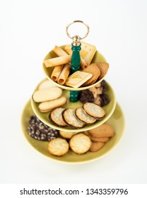 Three Tier  Selective Focus Serving Dish with Yellow Glazed Plates  and Green Bakelite Stem with Brass Ring Handle for Desserts or Appetizers with Tea Time Cookies.