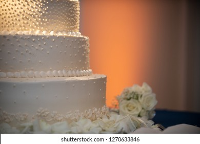 Three tier wedding cake with warm uplighting close up
