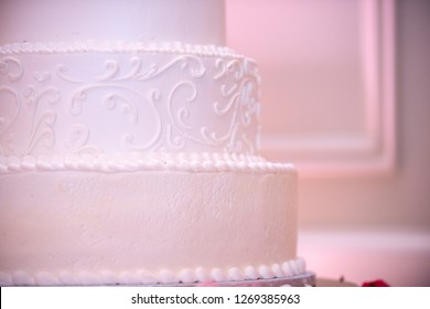 Three tier white wedding cake with pink uplighting close up