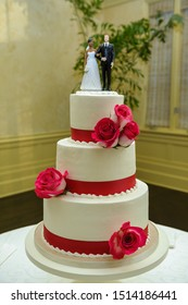 Three tier white wedding cake decorated with red roses and a  biracial couple as a cake topper, in South Louisiana.