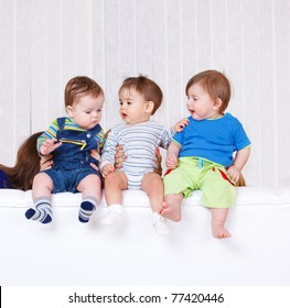Three toddlers sit on the sofa back