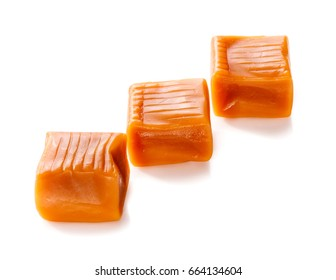three toffee caramel candies in row close-up isolated on white background