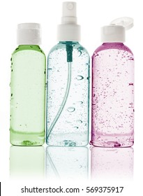 three toiletry bottles with water droplets on white background