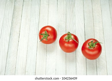 three tomatoes on white wooden table