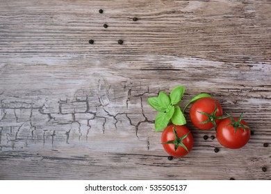 Three tomatoes and pepper groups with basil on the wooden table, view from above