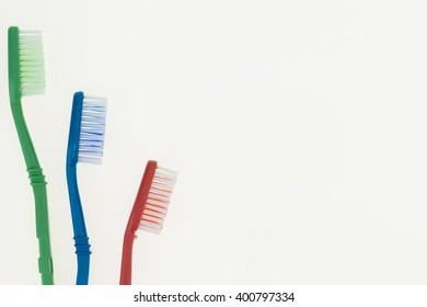 Three toothbrushes, on white background with copy-space