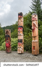 Three totem poles against a stand of green trees with cloudy sky
