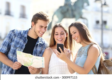 Three tourist friends consulting gps on smart phone in a touristic place with a monument in the background