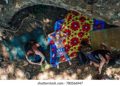 three tourist relax on the rug in the ground in shrilanka forest