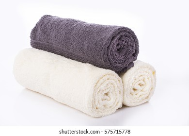 Three towels two white and one gray, rolled into a roll on a white background. Isolated / Three towels two white and one gray, rolled into a roll on a white background. Isolated / Nadale