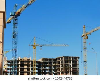 Three tower cranes near concrete building. Construction site.
