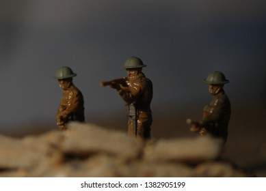 Three toy soldiers line up behind sandbags which are out of focus at the front of the frame, their rifles pointing into the camera.