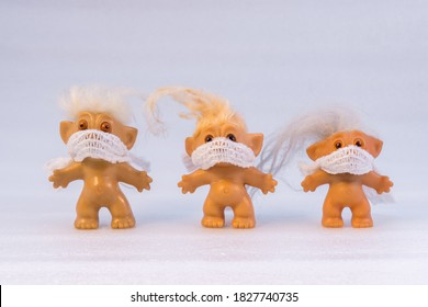 Three toy trolls wearing masks against white background