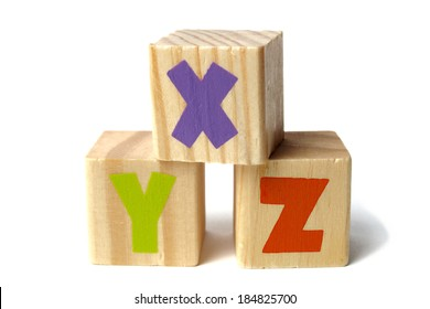 Three toy wooden blocks with letters XYZ on them