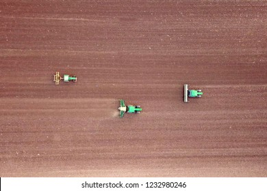 Three Tractors cultivating and seeding a dry field - Top down aerial image.