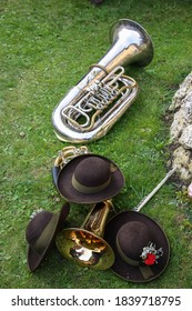 Three traditional Austrian fedoras and two brass instruments on green grass, alpine music background