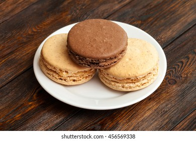 Three traditional french chocolate macarons on plate, dark wooden background