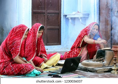 Three traditional Indian young married women working in traditional kitchen on laptop. Using technology in rural households. Women cook food and learn technology. Rural women using Laptop.