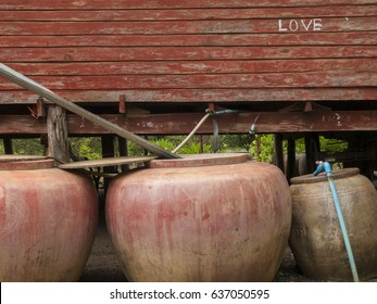 Three traditional, large water containers outside a wooden Thai house in Kanchanaburi, Thailand. The word 'love' is written in the wall of the house.