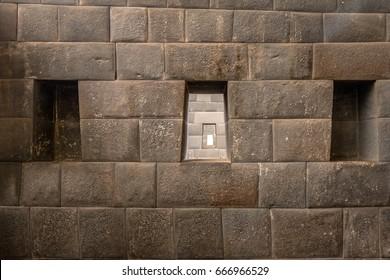 The three trapezoidal windows and Inca Wall of Rainbow Temple at Qoricancha Inca Ruins - Cusco, Peru
