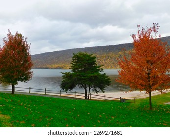 Three trees in autumn foliage with lake and Appalachian Mountains in the background.  Image taken at Seven Points, Lake Raystown Region, Pennsylvania.