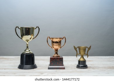 Three trophys with difference size and design on vintage wooden table.Step or process to be successful.