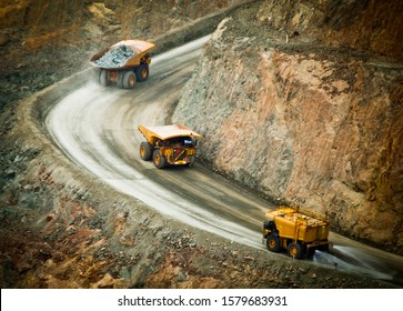 Three trucks in a busy modern gold mine in Kalgoorlie, Western Australia. One water truck and two large haul truck transport gold ore from open cast mine. - All logos removed.