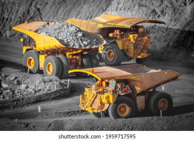 Three trucks in a modern gold mine in Australia. Spot color large haul trucks transport gold ore from the pit, Opencast mine. Yellow trucks, black and white background. All logos removed.