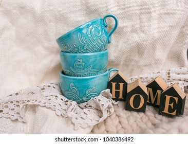 Three turquoise cups for tea or coffee with a ship on it stand with three wooden letters 'Home' on the beige tablecloth