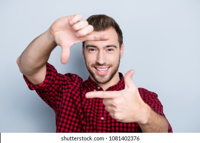 Three, two, one, smile! Close up portrait of cheerful glad with toothy smile man making a frame using his hands and fingers, trying to find perfect good sight, isolated on gray background