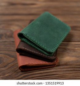 Three two-pocket leather handmade cardholder. Cardholders lies one on another. Stock photo on blurred background.