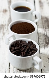 Three types of coffee - ground, grain and beverage in cups on white table, vertical, closeup