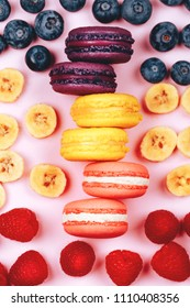 Three types of fruit macarons: raspberry, banana and blueberry. Flat lay style. Pink background, flat lay style.