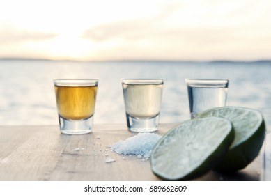 Three types of tequila on beach table with lime and salt overlooking scenic ocean.