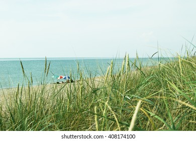 Three umbrella from the sun on the quiet beach of the Baltic Sea. Curonian Spit in the greenery, July Nida and Juodkran