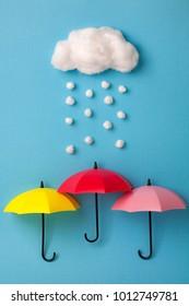 Three umbrellas under the cloud on sky blue background