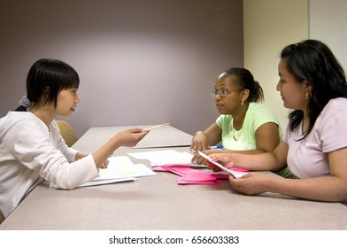 three undergraduate college students having a discussion about an assignment in a work room at the school library, Brooklyn, NY, June 25, 2016