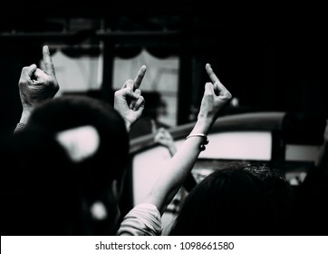 Three unidentifiable protestors give the middle finger, rude gesture.
