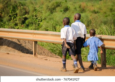 Three unidentified African Schoolchildren walking along the dangerous highway. Road accidents are prone in Africa due to lack of control and few licensed drivers