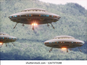 Three unidentified flying objects over a forest with trees and mountains behind.