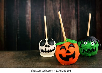 Three unique Halloween candy apples against a dark wood background. Skeleton, jack o lantern and monster.