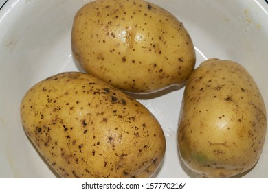 Three unpeeled washed potatoes in a white plate. Home cooking. Close up