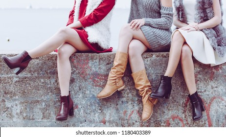 Three unrecognizable fashionable women wearing stylish shoes outdoor. Boots perfect for autumn and winter