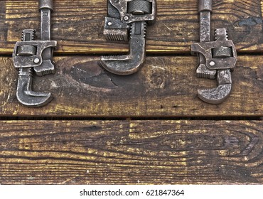 Three upside down antique wrenches on rough wooden background