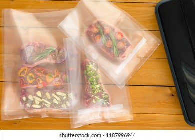Three vacuum packed bags of flat iron steaks alongside the sealer machine each with a different seasoning and flavor ready for freezing or sous-vide cooking