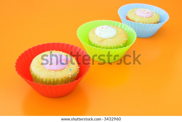 Three vanilla muffins with icing in plastic cups, with yellow fork on grass table against orange wall.