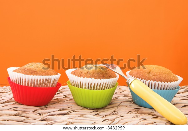 Three vanilla muffins in plastic cups, with yellow fork on grass table against orange wall.