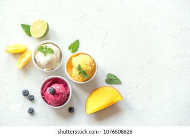Three various fruit and berries ice creams on white background, copy space. Frozen yogurt or ice cream with lemon, mango, blueberries - healthy summer dessert.