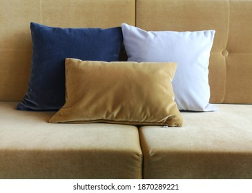 Three velvet cushions on a velvet sofa in the colors blue, yellow and white.